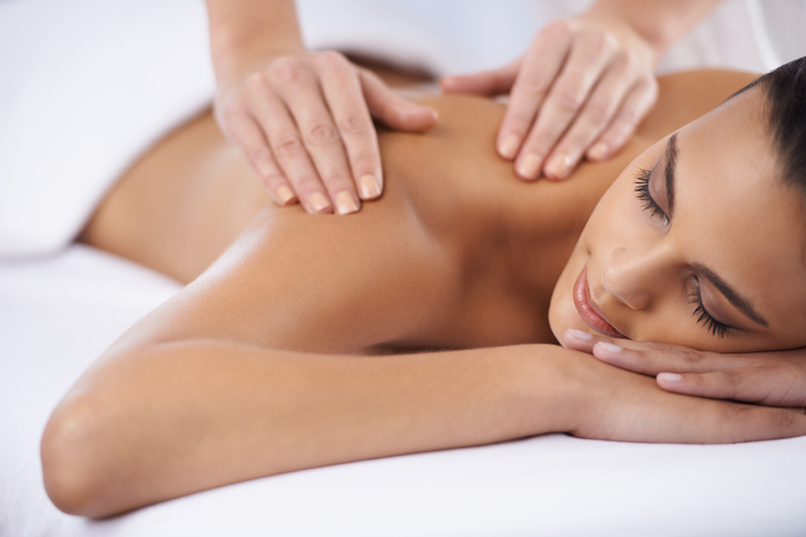 A young woman receiving a massage from a massage professional